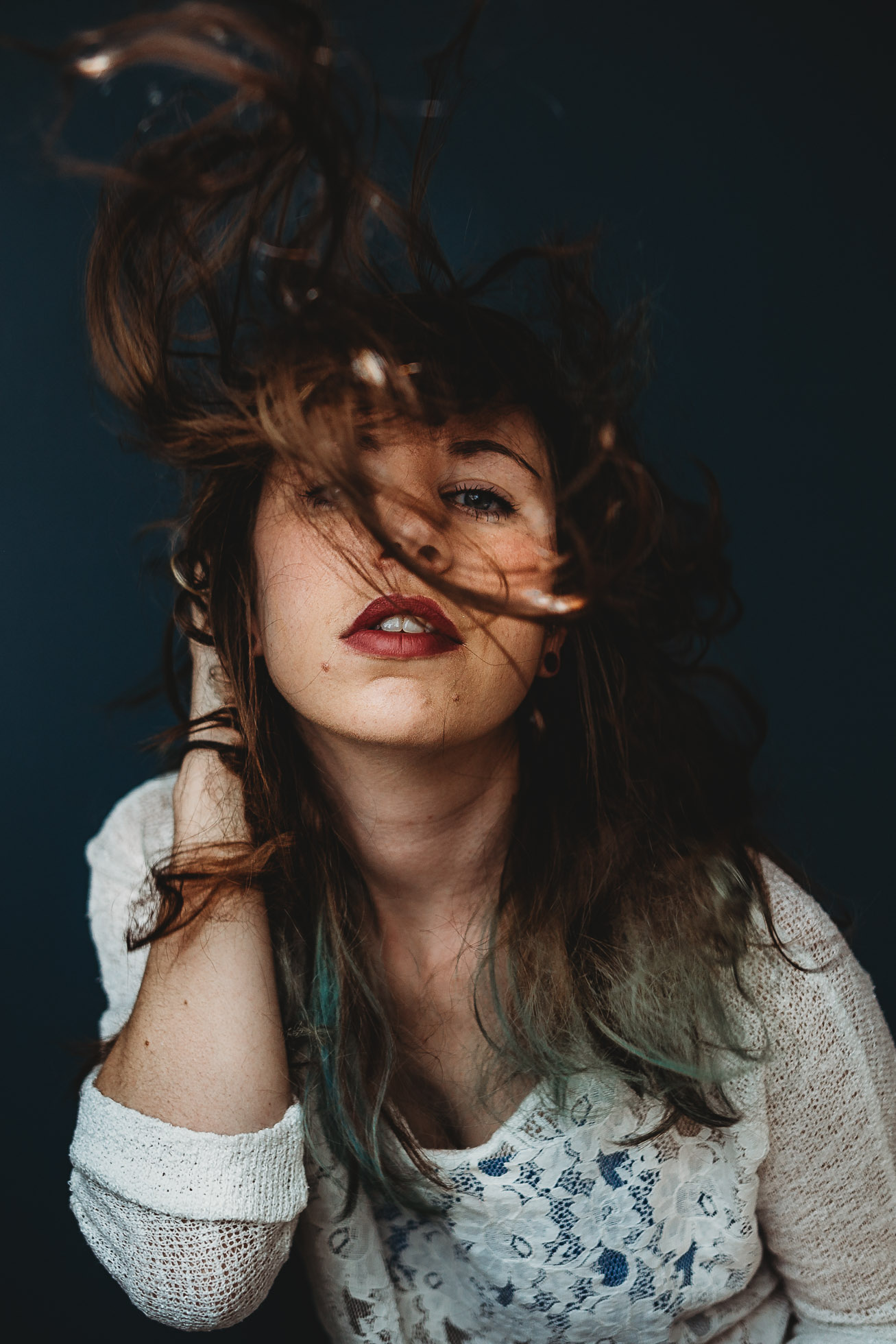 Self-Portrait-Of-A-Woman-Against-A-Blue-Background-With-Hairflip-2
